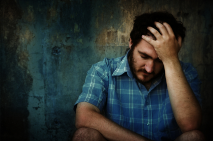 man with depression sitting down holding his head up