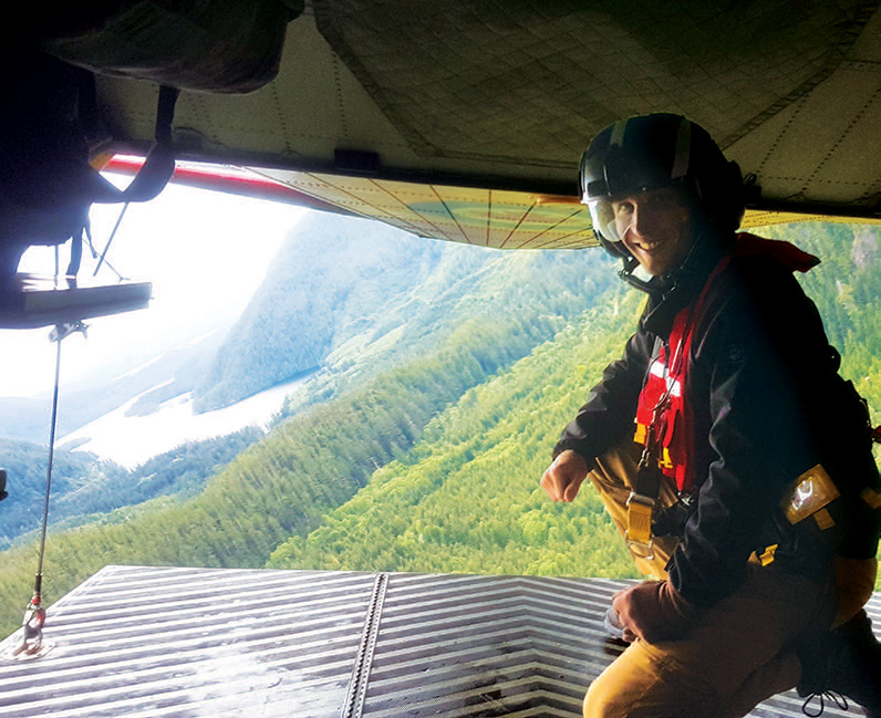 Dr Obert on the open ramp of the CH-149 Cormorant as it navigates a valley on Vancouver Island.