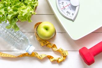 Healthy lifestyle concept with an apple, a head of lettuce, a bottle of water, a tape measure, a weight, and a scale
