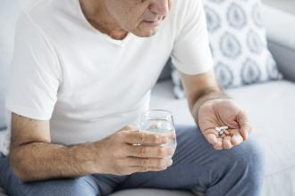 A senior man is sitting down, with a glass of water in one hand and a few different pills in the other
