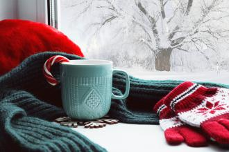 A table by the window with gloves, a scarf, and a mug with a candy cane in it