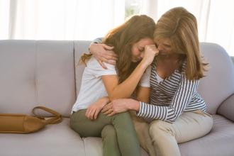 A mother comforts her teen daughter, who is upset