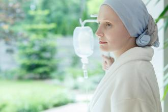 A cancer patient with a scarf on her head and an IV