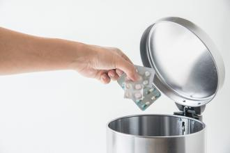 A hand is shown putting medication into a garbage can