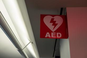 "A sign with the abbreviation ""AED"" hangs in a hallway"