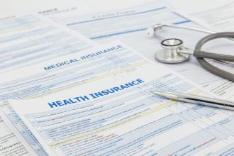 A stethoscope sits on top health insurance paperwork