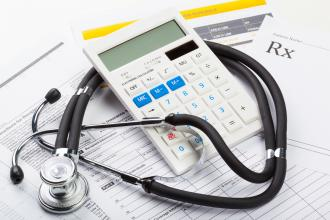 A stethoscope and calculator sit on top of medical paperwork