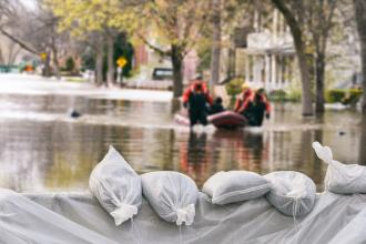 Rescuers traverse a flooded street by boat; sandbags are seen in the foreground