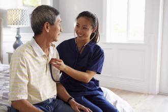 A doctor consults with a patient in their home