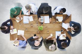 A top view of a medical team sitting around a boardroom table