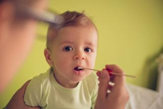 A doctor holds a swab at a baby's open mouth.