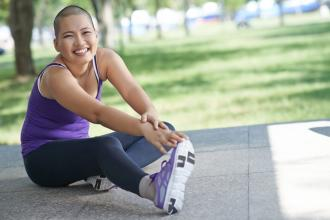 An almost-bald woman smiles at the camera while stretching in a park.