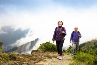 A senior couple is walking on a trail