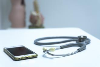 A stethoscope and a smart phone on a desk