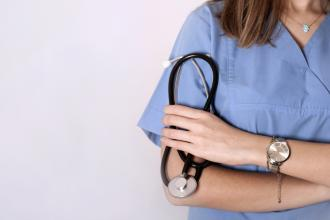 A doctor stands against a wall, holding a stethoscope