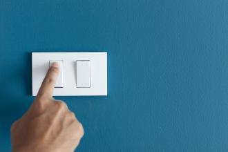 A hand presses a light switch