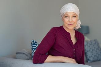A woman with a scarf on her head sits on a bed