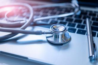 A stethoscope sits on top of a computer keyboard
