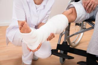 A patient sits in a wheelchair, with a cast on their ankle