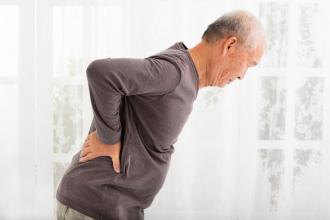A man bends forward from back pain
