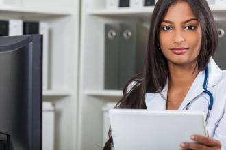 A health care administrator works at a computer