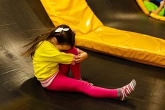 A young girl sits on a trampoline, holding her knee.