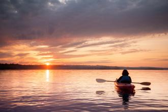 A woman in a kayak faces a sunset.