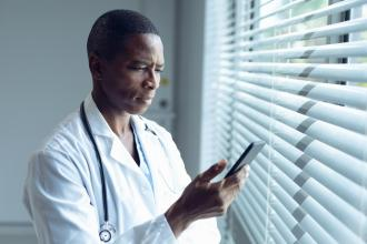 A doctor texting by a window with a serious expression.