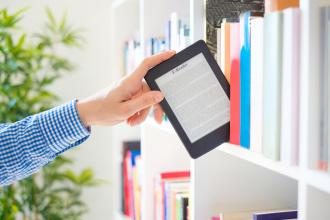 A hand pulls an e-reader from a shelf of books.