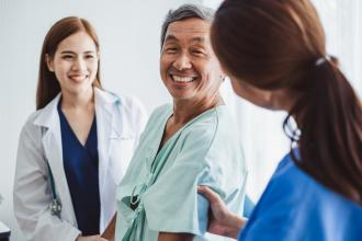A doctor and nurse smile with a happy patient.