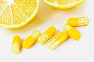 A close up of a lemon cut in half with yellow capsules.