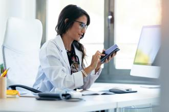 Doctor browsing on her smartphone at her desk