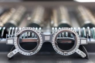 A pair of ophthalmologist test glasses in front of rows of lenses