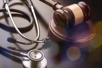 Wooden judge gavel with medical stethoscope close-up