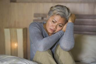 Depressed middle-aged female, sitting on bed