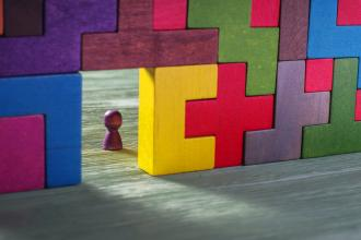 Colourful wall of wooden puzzle pieces with a wooden game piece set in an open rectangle space in the wall
