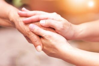 A pair of hands clasping another person's hand