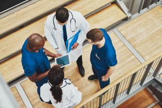 Multiracial medical team standing together around a tablet, overhead view