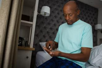 Senior man holding medicines while sitting on bed at home