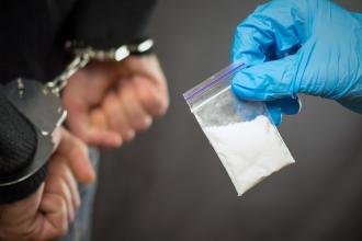 A man with drugs is being handcuffed