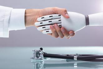 A doctor shakes a robotic hand