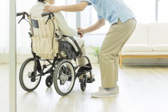 An aide assists a senior using a wheelchair