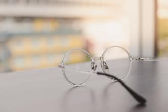 A pair of glasses sits on a table