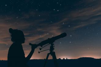 An astronomer looks at the night sky through a telescope
