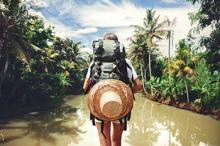 A backpacker walks through a rainforest