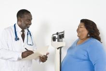 A doctor talks to an overweight patient and writes notes in a folder