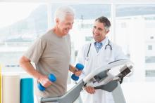 A man exercises while his doctor stands beside him
