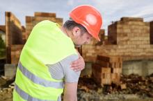 A construction worker holds his shoulder in pain