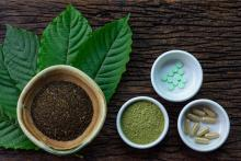 Kratom leaves beside dishes containing two different powders and two types of pills