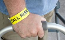 "A man with a wristband that reads ""fall risk"" stands using a walker"